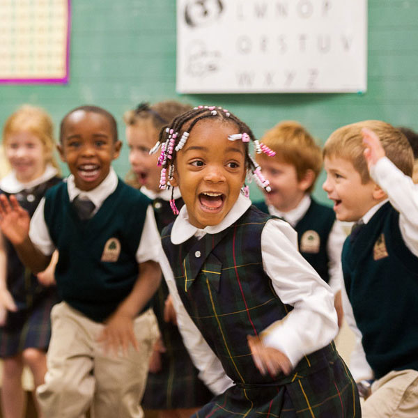 Pre-K students playing and smiling in class