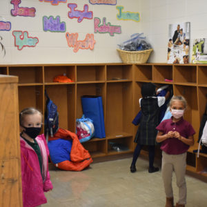 Students practicing the habit of responsibility by putting their belongings away
